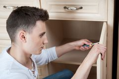 Young man assembling furniture Royalty Free Stock Photography
