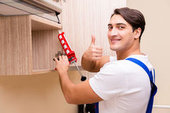 The young man assembling kitchen furniture. Young man assembling kitchen furniture Stock Image