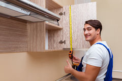 The young man assembling kitchen furniture Royalty Free Stock Image