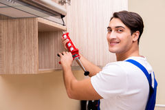 The young man assembling kitchen furniture Stock Image