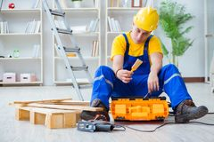 The young man assembling wood pallet. Young man assembling wood pallet royalty free stock photography