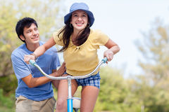 Young man assisting young woman on bike Stock Photos