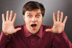 Young man with astonished expression and hands up Stock Photos