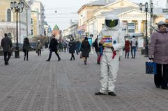 A young man in an astronaut suit, handing out leaflets on the street . royalty free stock images