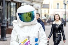 A young man in an astronaut suit, handing out leaflets on the street . stock images