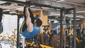 Young man athlete doing pull-up bar abdominal exercise in gym. Wide angle stock images
