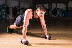Young Man Athlete Doing Pushups With Dumbbells As Part Of Bodybuilding Training. Young Man Athlete Doing Pushups With Dumbbells As Part Of Bodybuilding Training stock photos