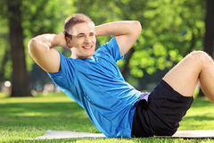 Young man athlete exercising abs in a park Stock Images
