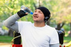 A young man athlete with headphones on his head drinking water after a hard workout on the street. Guy smiles receiving pleasure stock images