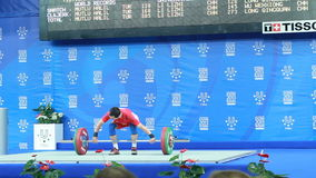 Young Man Athlete Lifts up Weight on Brightly Lit Stage. KAZAN, TATARSTAN/RUSSIA - MAY 15 2013: Young man athlete in red trico lifts up weight on brightly lit stock video footage