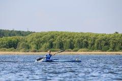 Young man athlete on rowing kayak on lake Stock Images