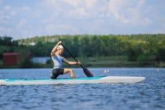 Young man athlete on rowing kayak on lake Royalty Free Stock Images