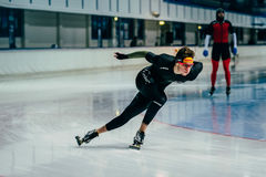 Young man athlete skater rolls through curve rink during warmup Stock Images