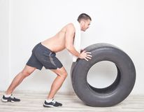 Young man athlete. With a white towel rolls a big wheel for training crossfit against the background of the wall royalty free stock photography