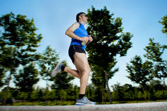 Young man with athletic runner legs holding isotonic energy drink while running in city park Stock Image