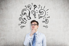 Young man attacked by question mark sketches Royalty Free Stock Images