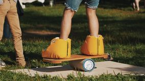Young man attempts to balance board on a cylinder while wearing giant boots stock video footage