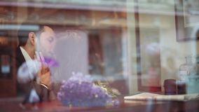 Young man and attractive brunette European woman in the white dress passionately kissing in the cafe by the window in a stock footage