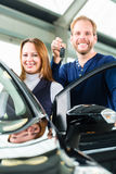 Young man with auto in car dealership Stock Photo