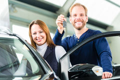 Young man with auto in car dealership. Young men beside a new car in car dealership, obviously he is buying the auto, or making a test drive and holding the keys Stock Images