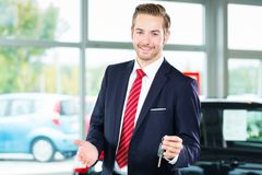 Young man or auto dealer in car dealership. Seller or car salesman in car dealership with key presenting his new and used cars in the showroom stock photos