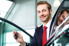 Young man or auto dealer in car dealership. Seller or car salesman in car dealership with key presenting his new and used cars in the showroom Stock Photography