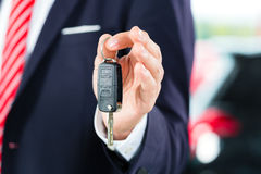 Young man or auto dealer in car dealership. Seller or car salesman in car dealership with key presenting his new and used cars in the showroom Stock Images