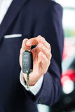 Young man or auto dealer in car dealership Stock Photo