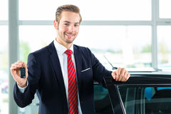 Young man or auto dealer in car dealership. Seller or car salesman in car dealership with key presenting his new and used cars in the showroom royalty free stock photo