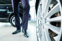 Young man or auto dealer in car dealership. Seller or car salesman in car dealership presenting the extra decorations like sport rims of his new and used cars in Royalty Free Stock Image