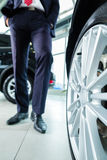 Young man or auto dealer in car dealership. Seller or car salesman in car dealership presenting the extra decorations like sport rims of his new and used cars in Stock Images