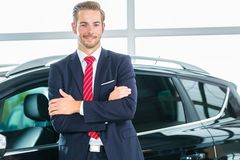 Young man or auto dealer in car dealership. Seller or car salesman in car dealership presenting his new and used cars in the showroom royalty free stock images