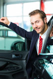 Young man or auto dealer in car dealership Stock Photos