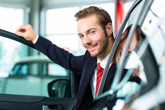 Young man or auto dealer in car dealership. Seller or car salesman in car dealership presenting his new and used cars in the showroom stock image