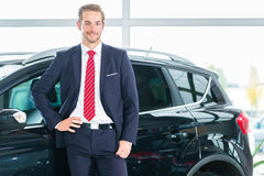 Young man or auto dealer in car dealership Royalty Free Stock Photo
