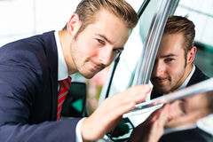 Young man or auto dealer in car dealership. Seller or car salesman in car dealership presenting the reflecting car paint of his new and used cars in the showroom Royalty Free Stock Image