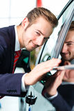 Young man or auto dealer in car dealership. Seller or car salesman in car dealership presenting the reflecting car paint of his new and used cars in the showroom Royalty Free Stock Photos