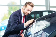 Young man or auto dealer in car dealership. Seller or car salesman in car dealership presenting the reflecting car paint of his new and used cars in the showroom Stock Photos