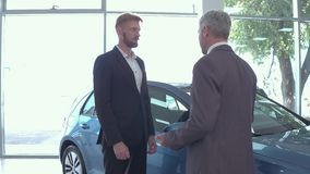 Young man at auto showroom talking with vehicle dealer. stock video