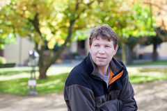 Young man in the autumn park sitting on bench Stock Photo