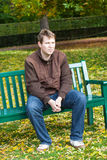 Young man in the autumn park sitting on bench Royalty Free Stock Images