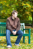 Young man in the autumn park sitting on bench Stock Image