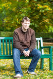 Young man in the autumn park sitting on bench Royalty Free Stock Photography