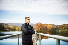 Young man in autumn park standing on pier. Royalty Free Stock Photo