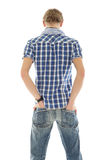 Young man back, hands in pockets Stock Images