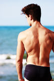 Young man from the back looking at the sea. A young man from the back looking at the sea. The guy has a muscular physique and well done. Her hair fashion. Its Royalty Free Stock Photography
