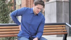 Young Man with Back Pain Sitting Outdoor on bench. 4k high quality, 4k high quality stock video footage