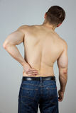 Young man with back pain. Young man touching his back for the pain Royalty Free Stock Image