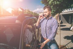 A young man on the background of car. Young attractive man with beard standing near his car and holding mobile phone royalty free stock photography