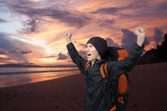 Young man on a background of sea sunset raised her hands up and screams. stock image
